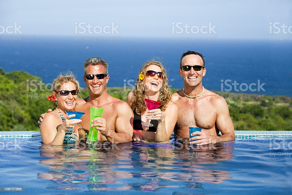 Toasting friends in pool royalty-free stock photo