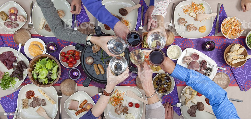 toasting over dining table with grilled meat and seafood stock photo