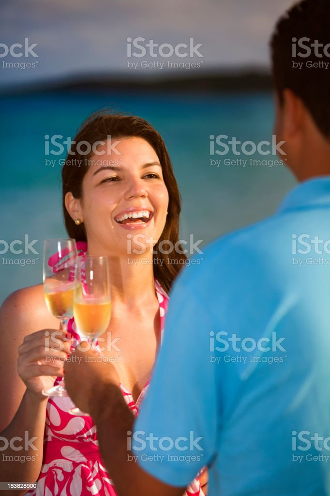Toasting with champagne flutes at sunset on tropical turquoise beach royalty-free stock photo
