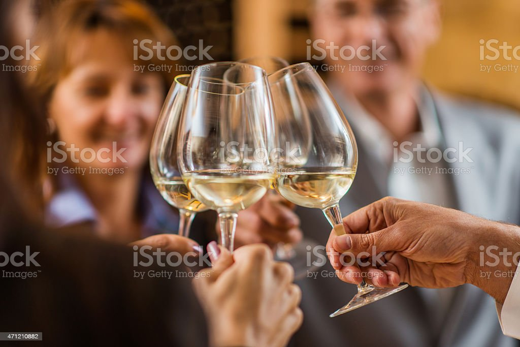 Toasting with white wine. stock photo