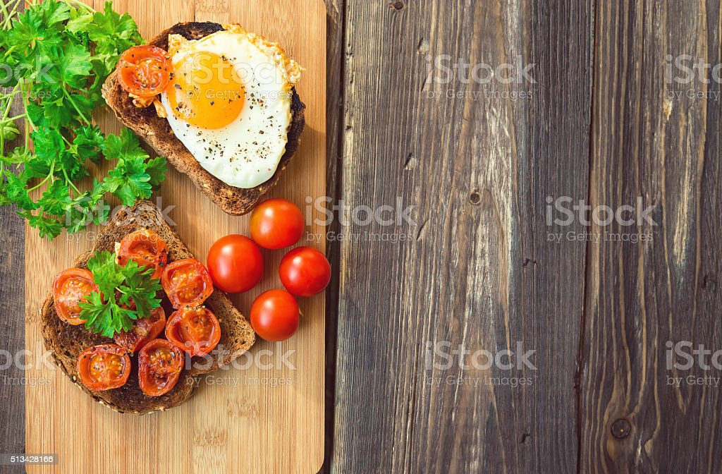 Toasts with egg and fried tomatoes stock photo