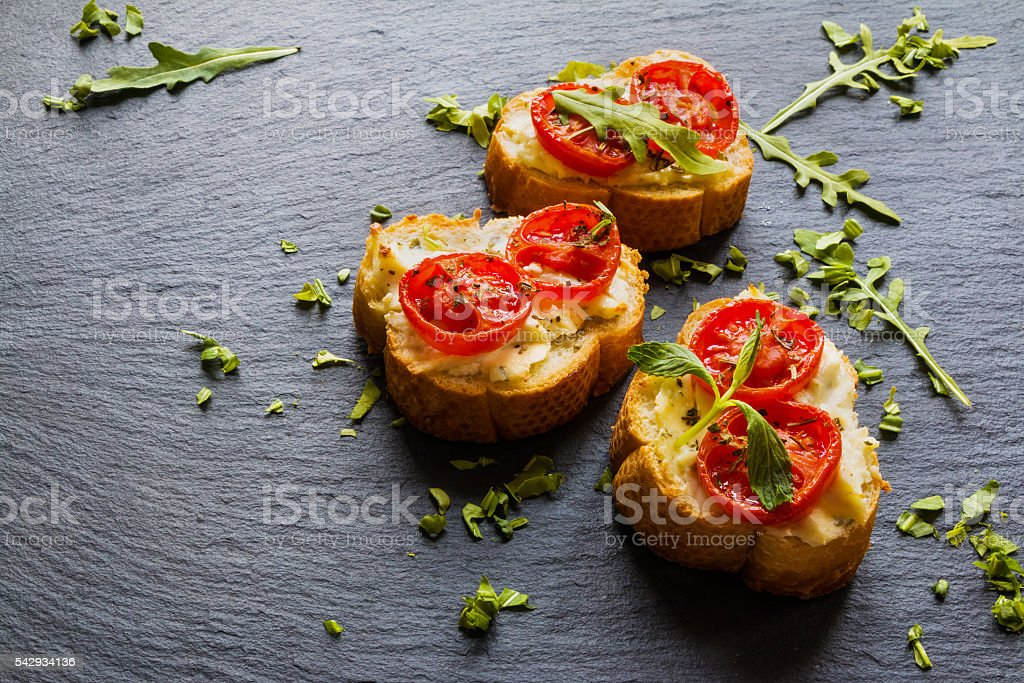 Toasts (Crostini) with ricotta, cherry tomatoes and arugula stock photo