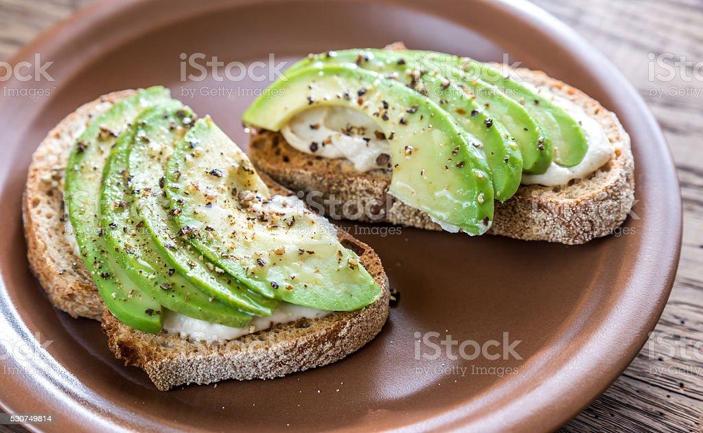Toasts with tahini sauce and sliced avocado stock photo