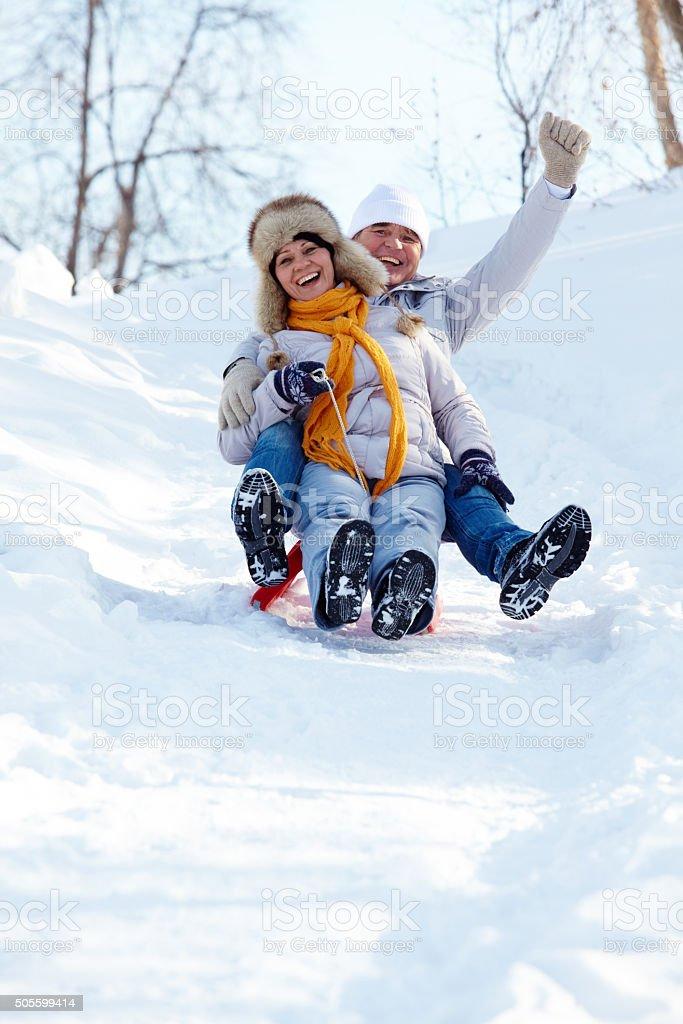 Tobogganing couple stock photo