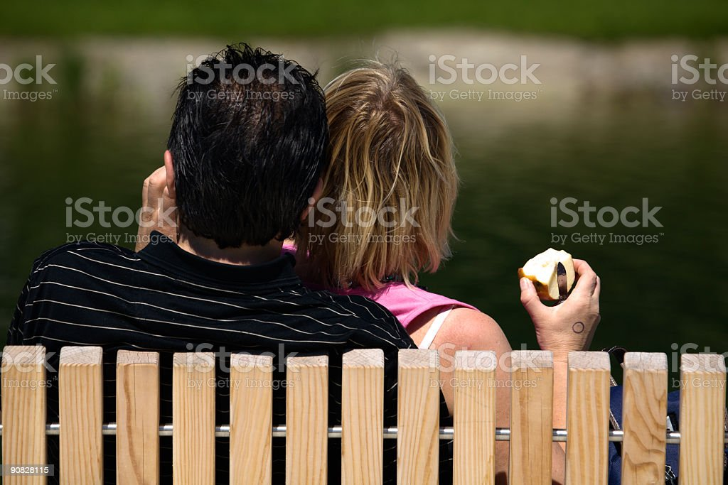 Young couple sitting on a bench in the sun, sharing an apple.