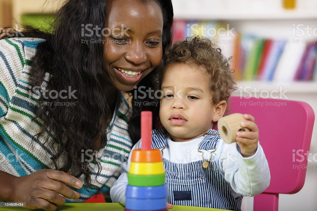 Toddler And Carer Playing With Multi-coloured Rings stock photo