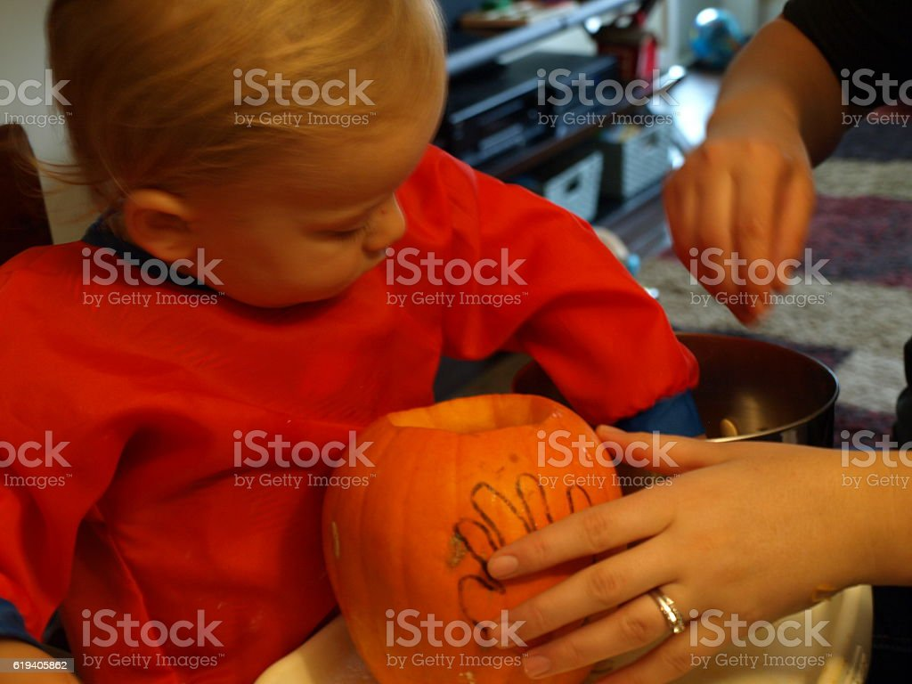 Toddler and mother clean out pumpkin to carve stock photo