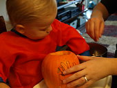 Toddler and mother clean out pumpkin to carve