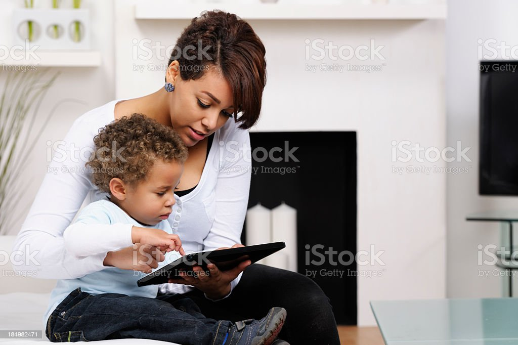 Toddler And Young Mother/ Sister Using A Digital Tablet stock photo