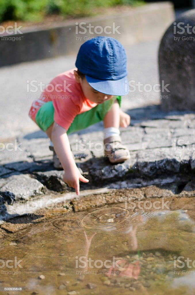 Toddler asian child Playing with the water stock photo