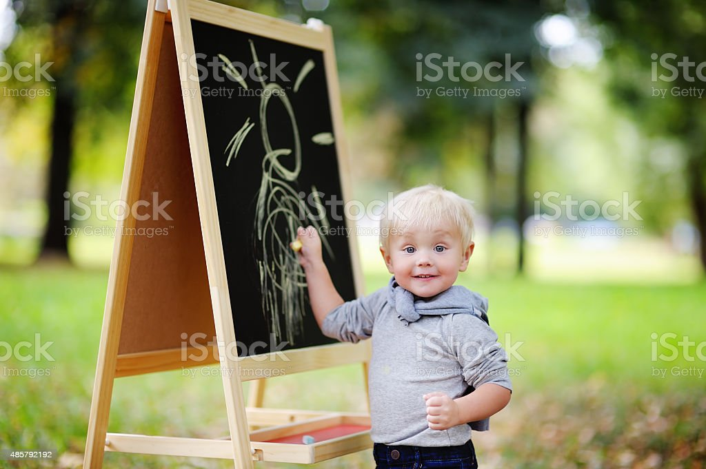 Toddler boy drawing standing by a blackboard stock photo