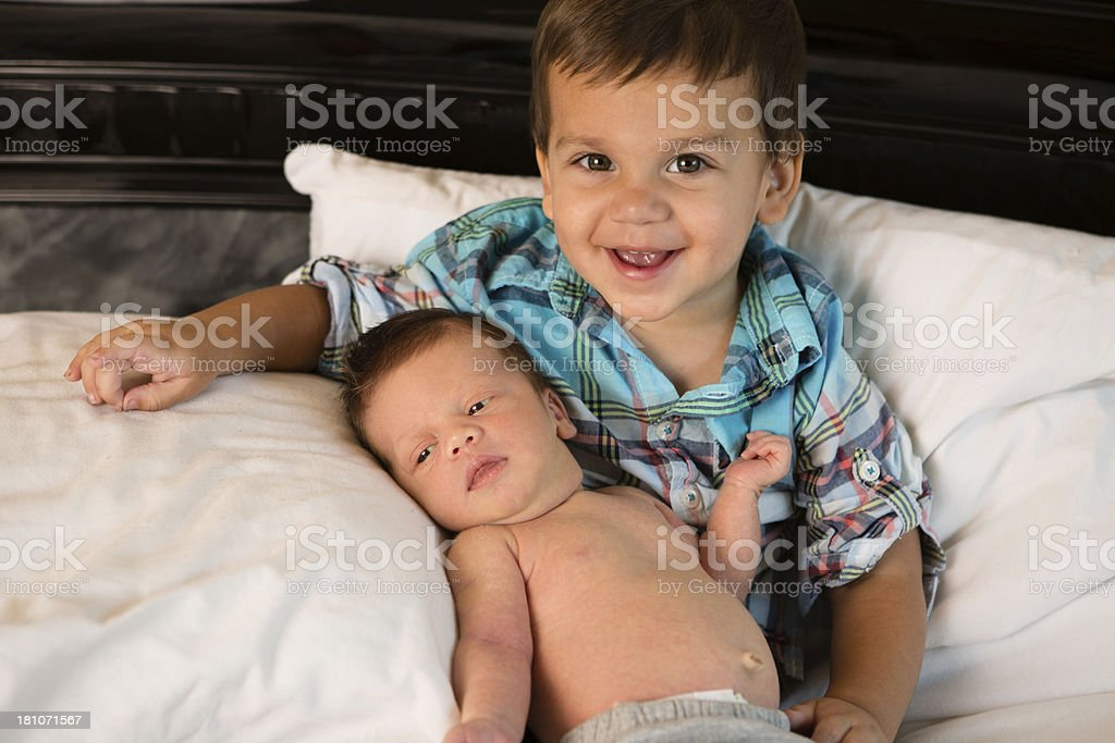 Toddler Boy Holding His Newborn Brother For First Time royalty-free stock photo