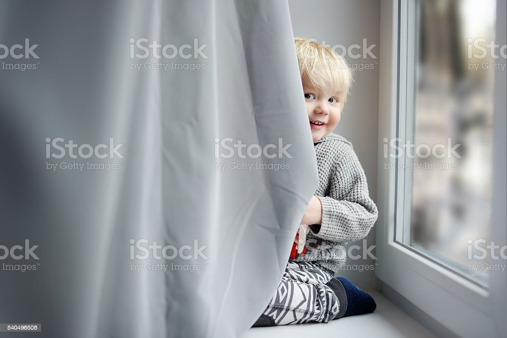 Toddler boy on the window sill stock photo