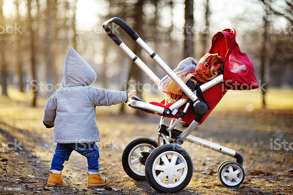 Toddler boy playing with his stroller stock photo