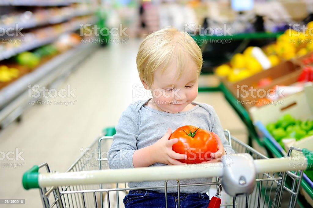 Toddler boy sitting at  shopping cart in a food store stock photo