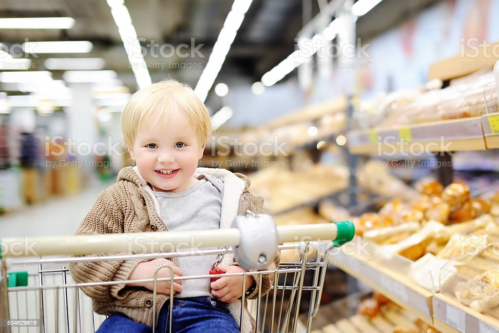 Toddler boy sitting in the shopping cart at supermarket stock photo