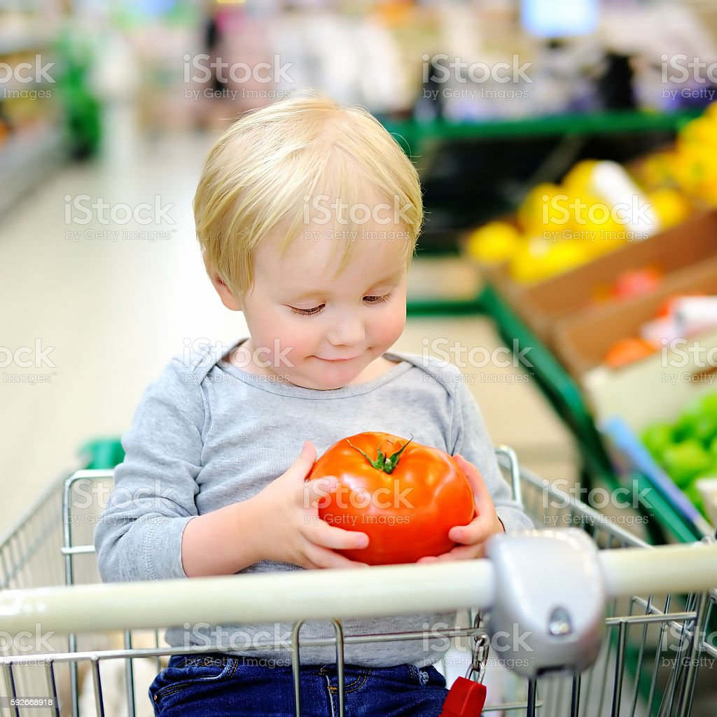 Toddler boy sitting in the shopping cart at upermarket stock photo