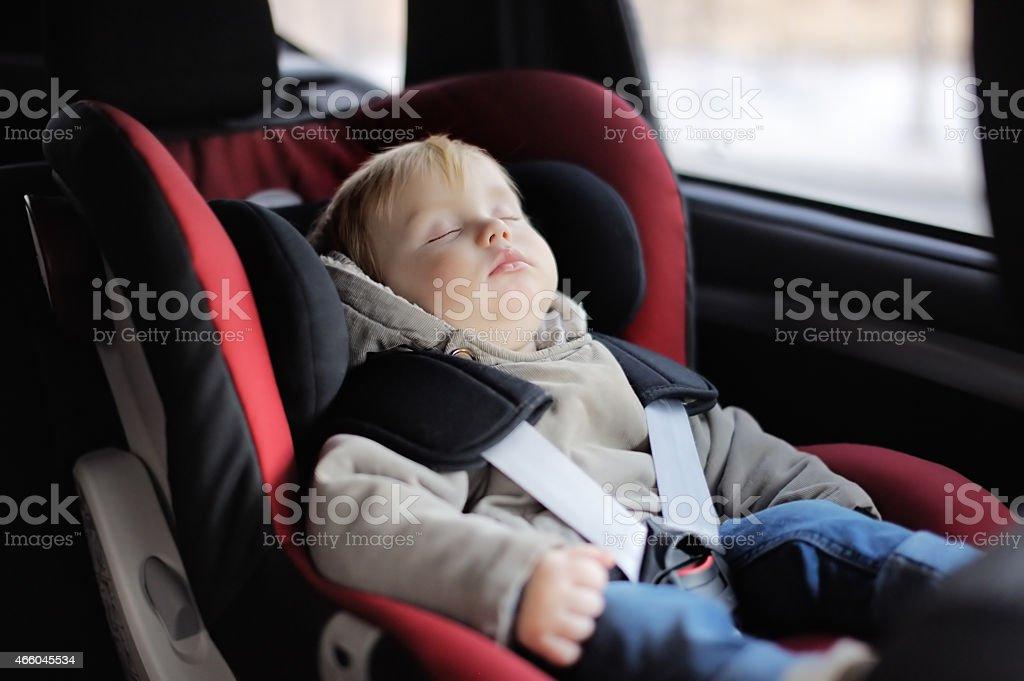 Toddler boy sleeping in car seat stock photo