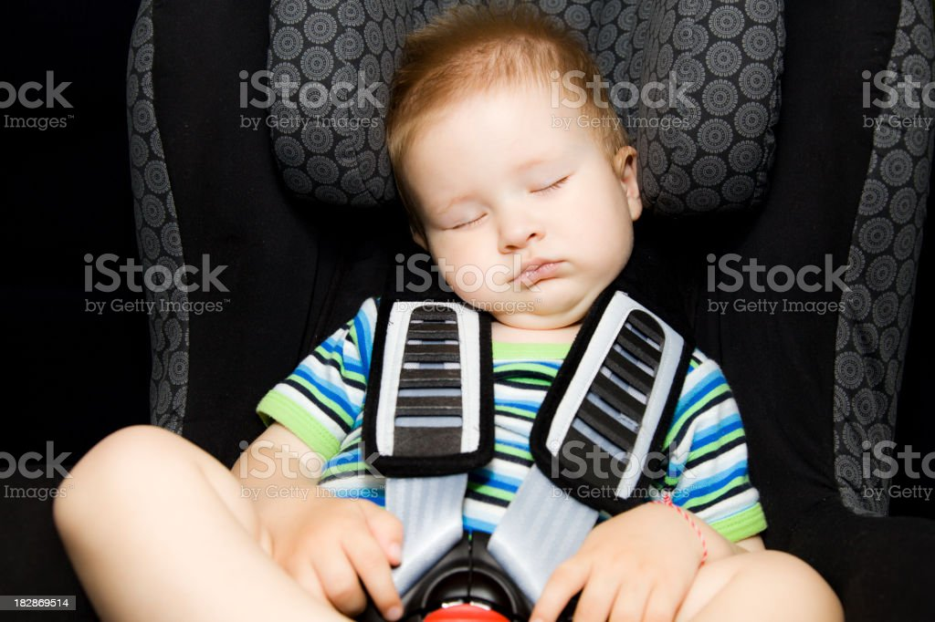 Toddler boy sleeping peacefully in his baby car seat. royalty-free stock photo