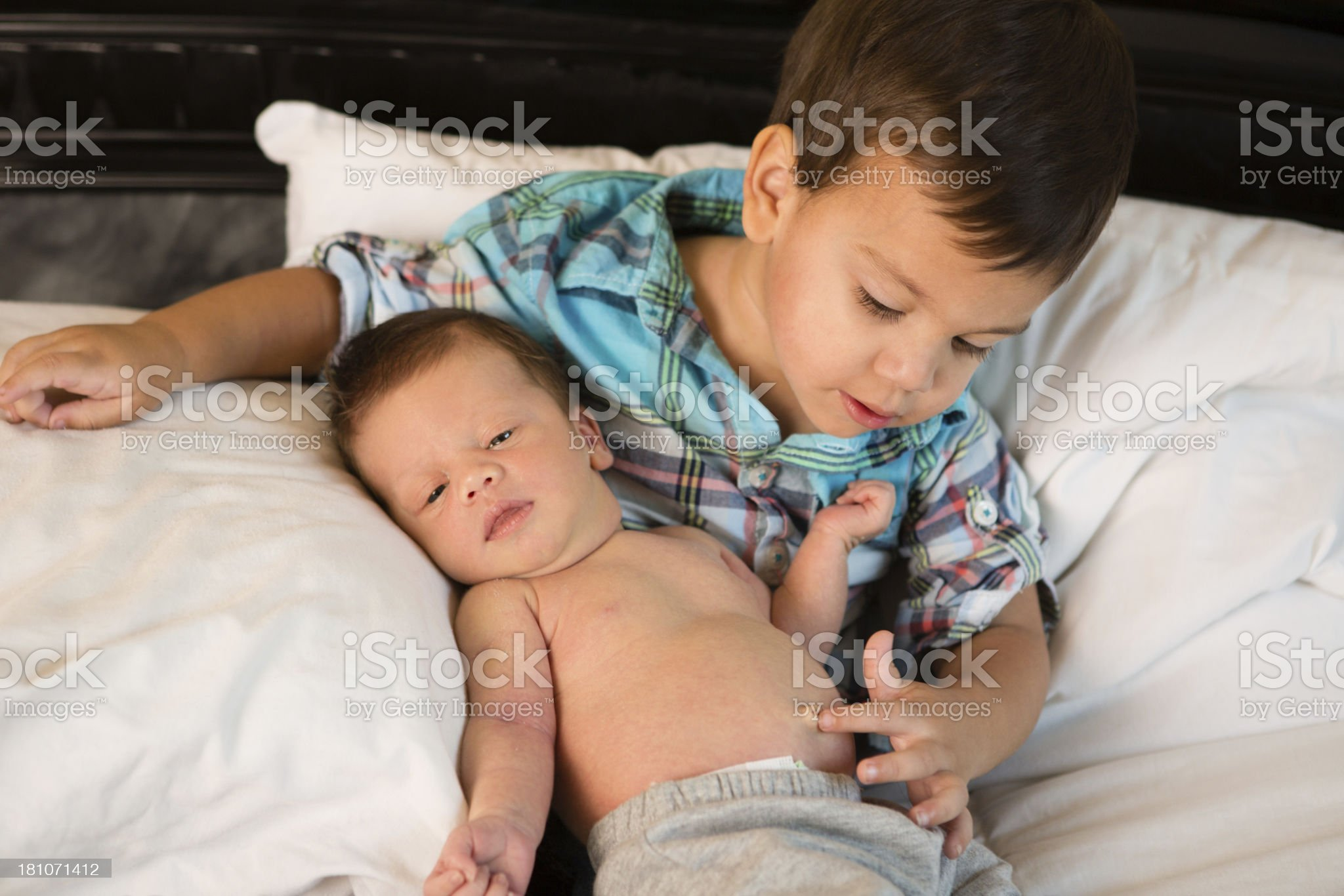 Toddler Boy Touching His Baby Brother's Belly Button royalty-free stock photo