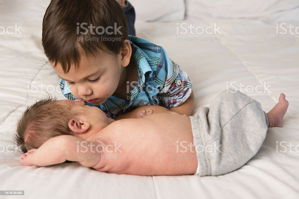 Toddler Boy Warming Up to His Newborn Brother royalty-free stock photo