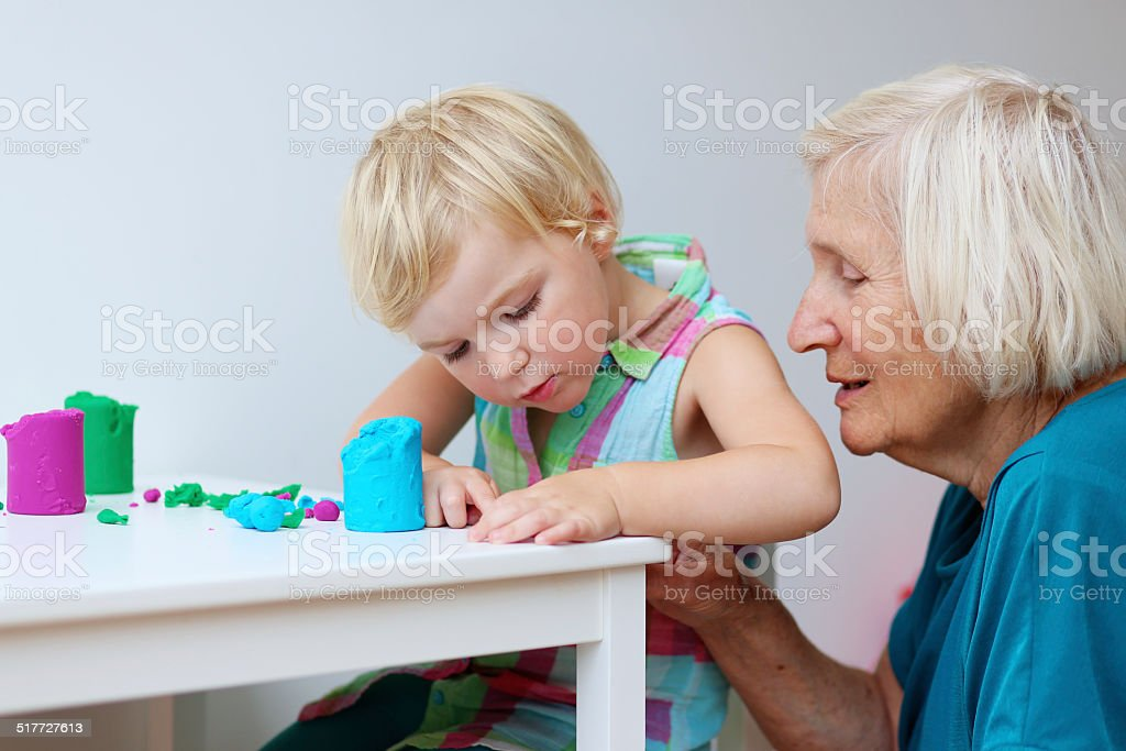 Toddler child and senior woman creating with plasticine stock photo