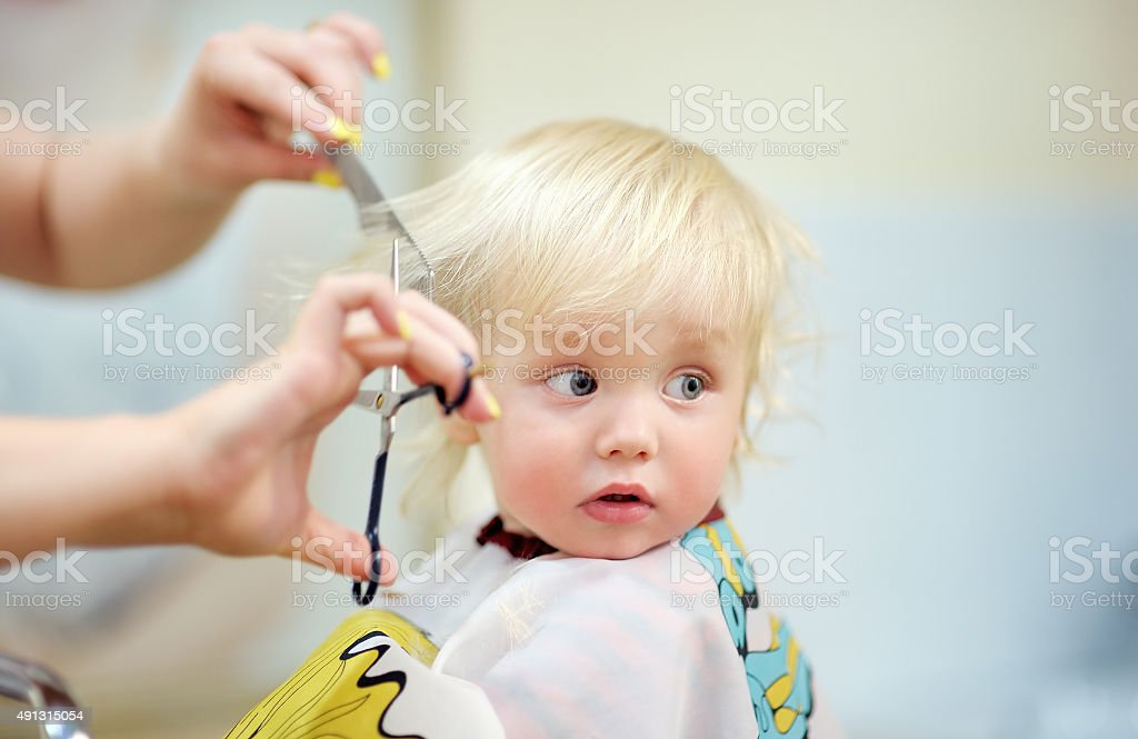 Toddler child getting his first haircut stock photo