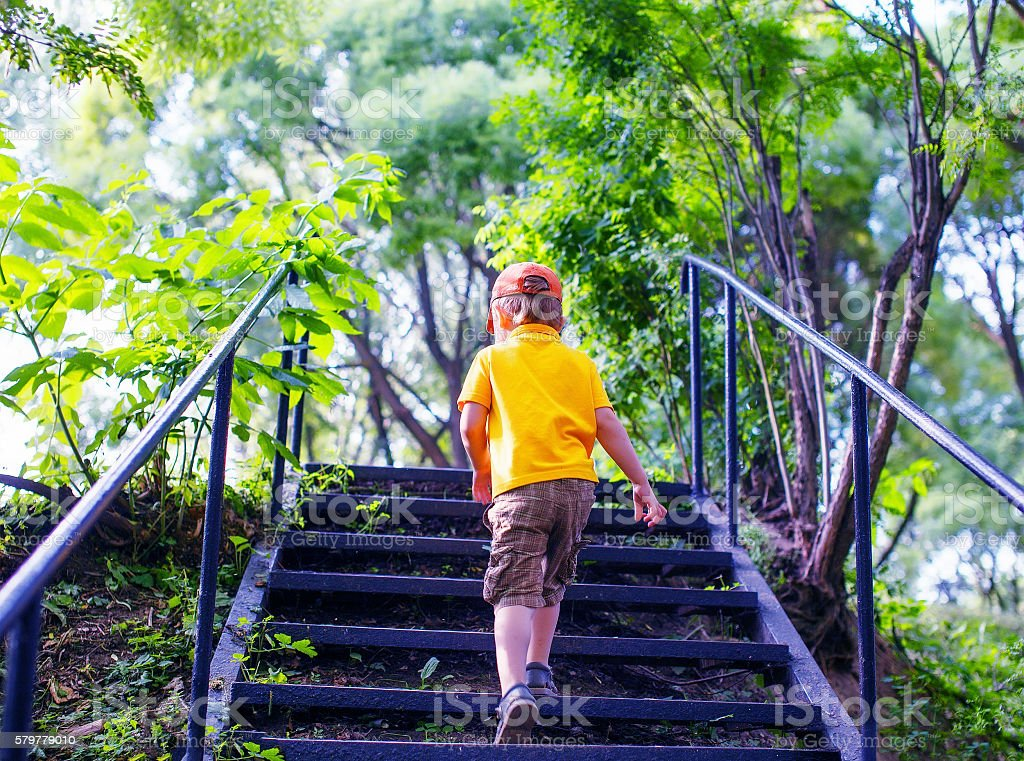 toddler climbs the stairs in the park stock photo