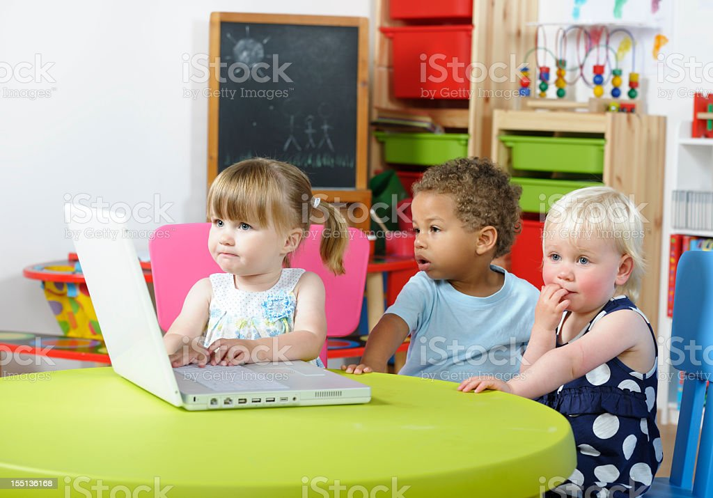 Toddler Contemplating While Peers Use Computer royalty-free stock photo