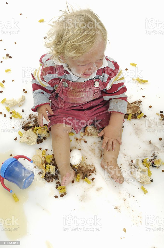 Toddler crying in a mess of food royalty-free stock photo