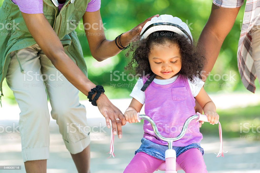Toddler daughter learning to ride a tricycle stock photo