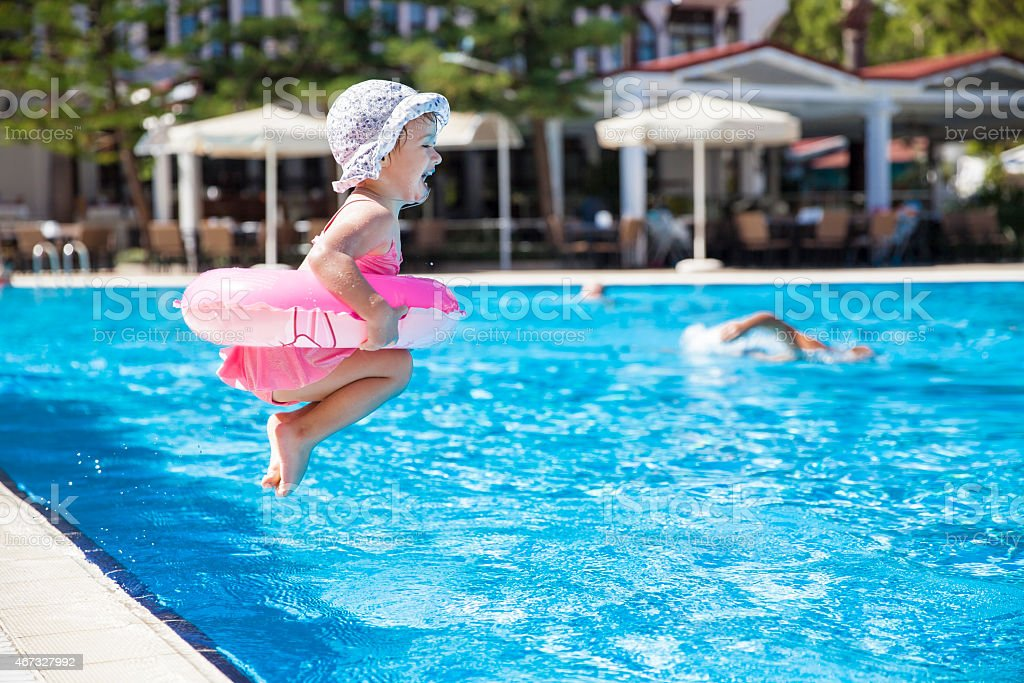 Toddler dressed in pink and jumping into a swimming pool stock photo