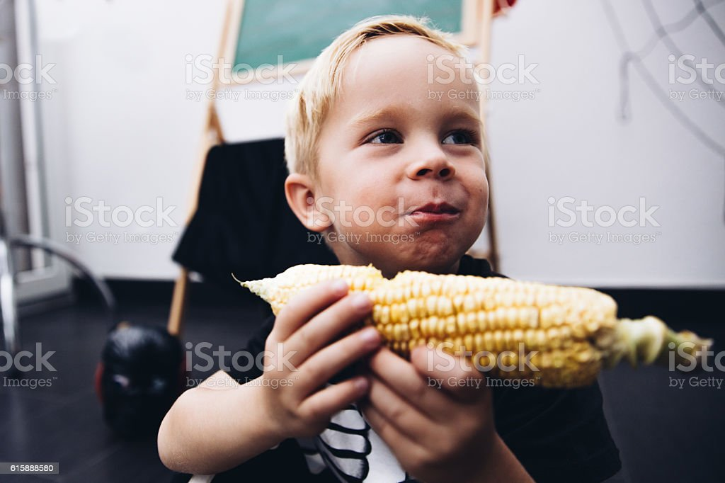 Toddler eating Corn Cob stock photo