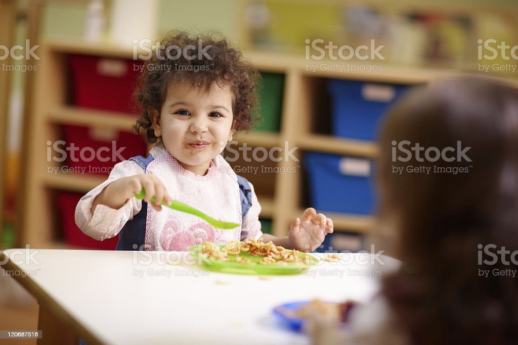 Toddler eating plate of food in daycare stock photo