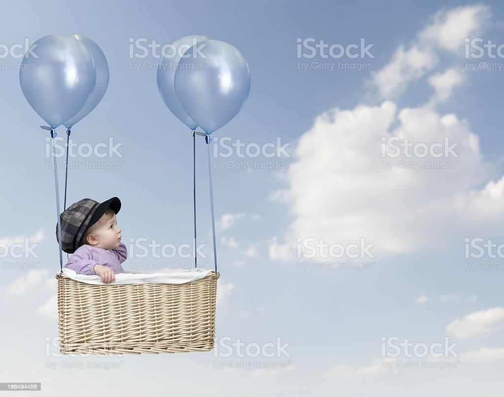 Toddler floating in a basket tied with balloons stock photo
