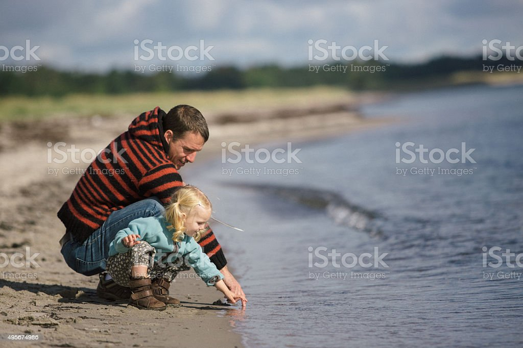 toddler girl and dad on the beach stock photo