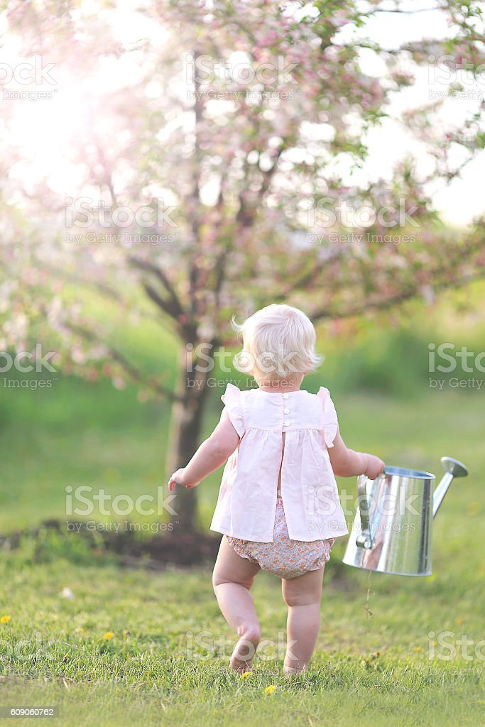 Toddler Girl Carrying Watering Can to Garden stock photo