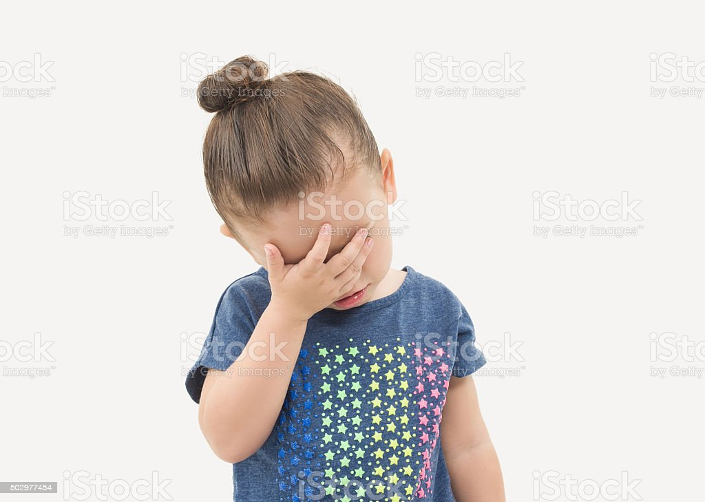 Toddler girl covering face with a sad expression stock photo