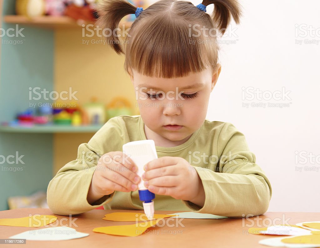 Toddler girl doing arts and crafts at preschool stock photo