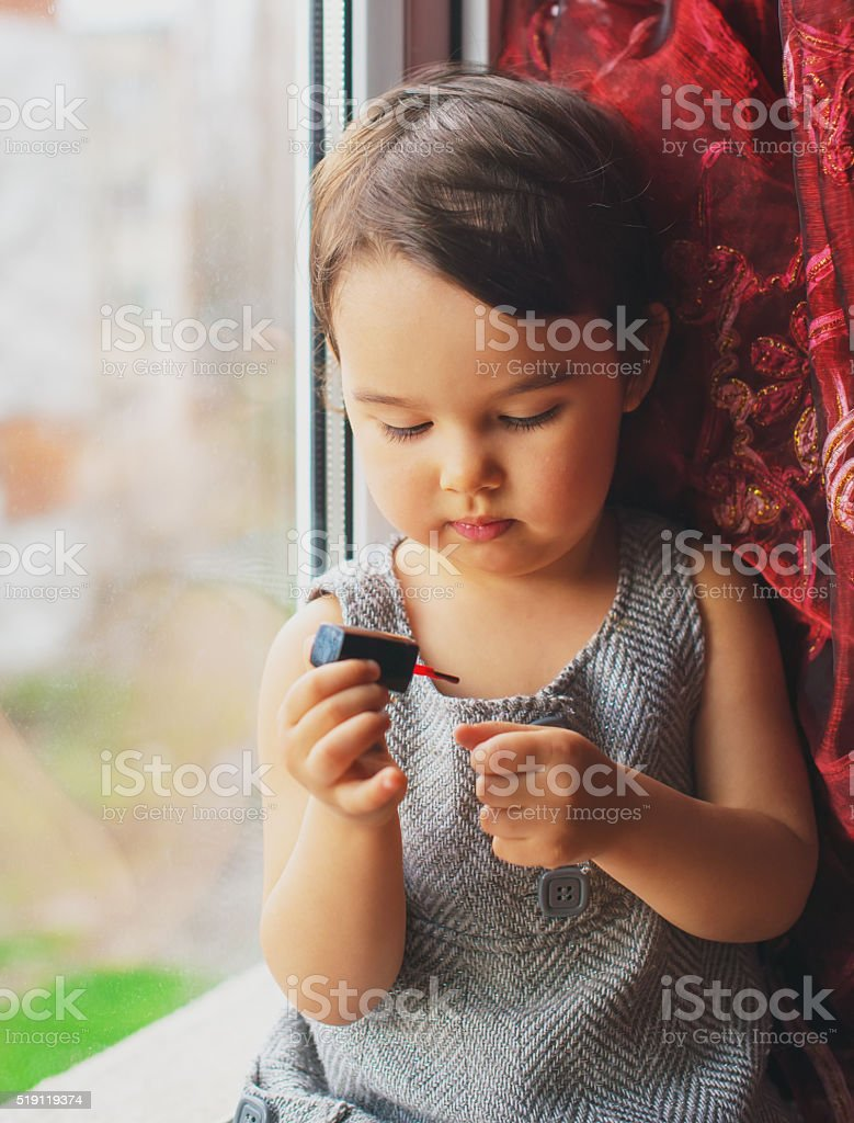 toddler girl having fun at home doing manicure stock photo