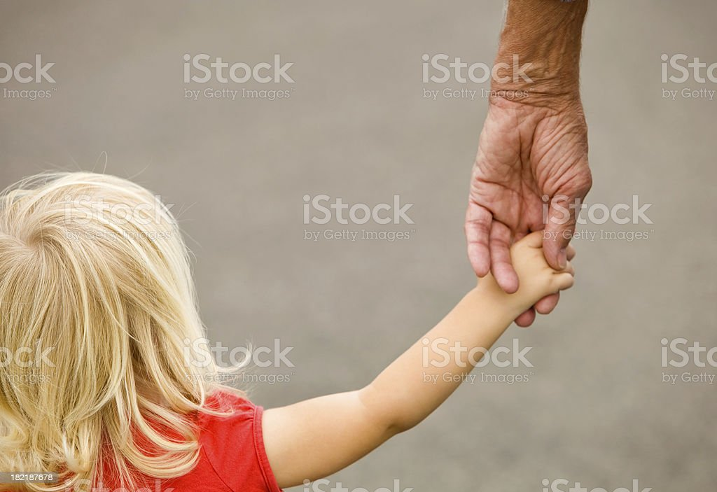 Toddler Girl Holding Grandfather's Hand stock photo