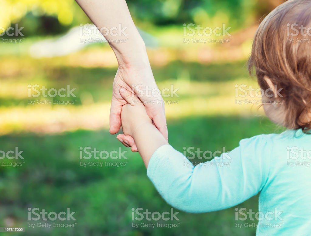 Toddler girl holding hands with her mother stock photo