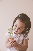 toddler girl holding young plants in eggshell, eco