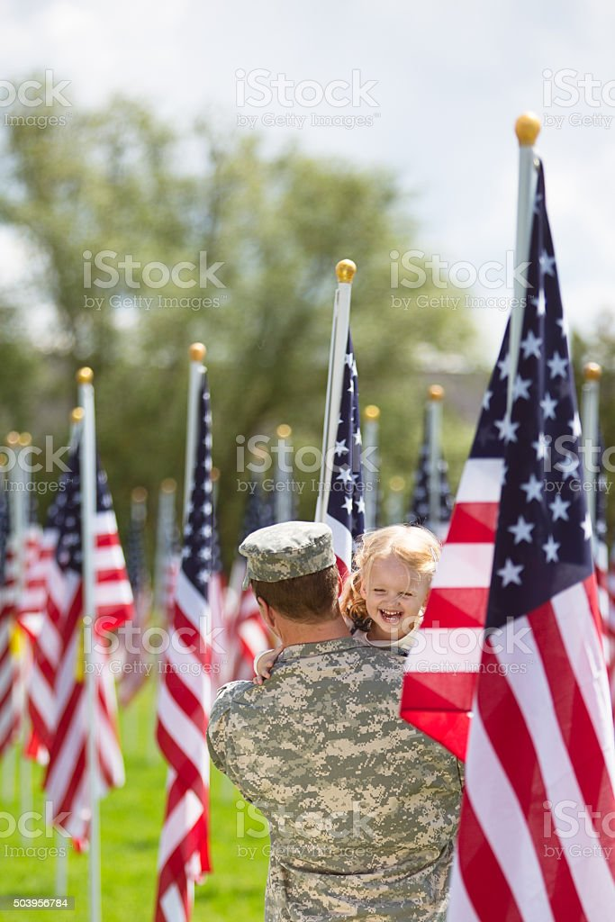 Toddler girl hugging her dad in uniform stock photo