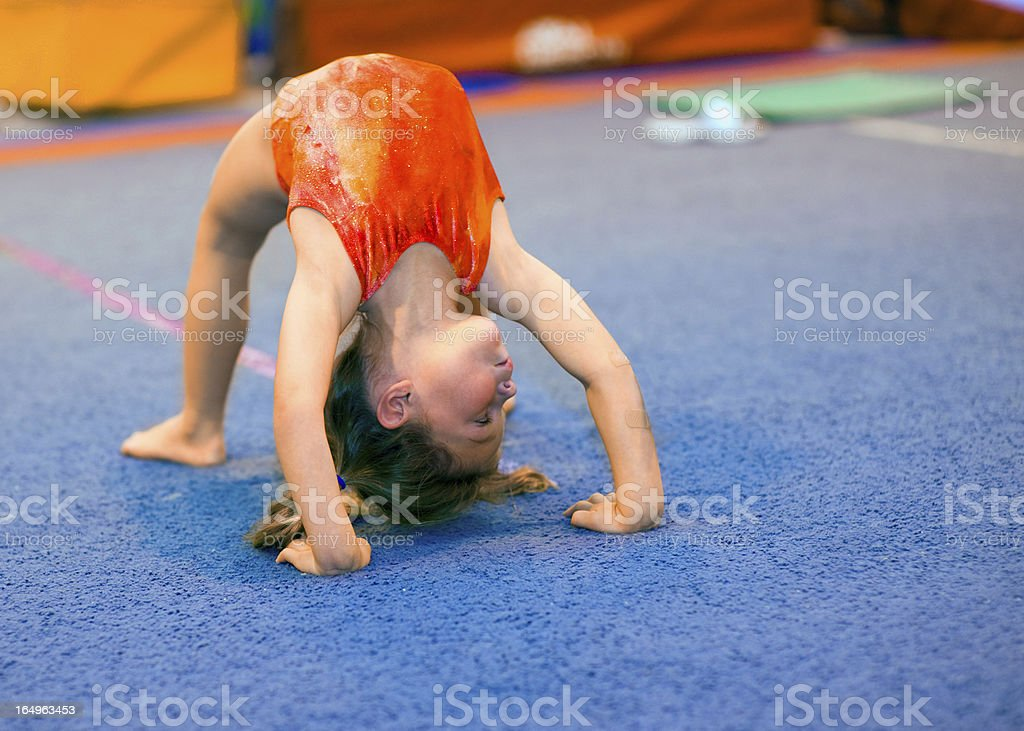 Toddler girl in leotard doing a bridge stock photo