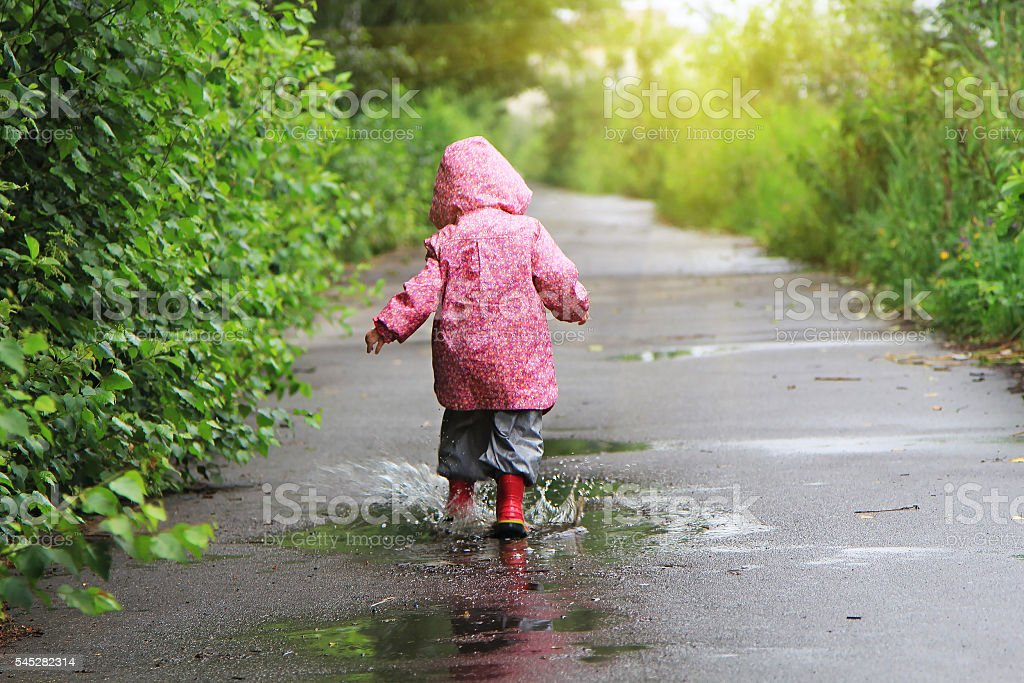 Toddler girl jumping in puddles after rain stock photo