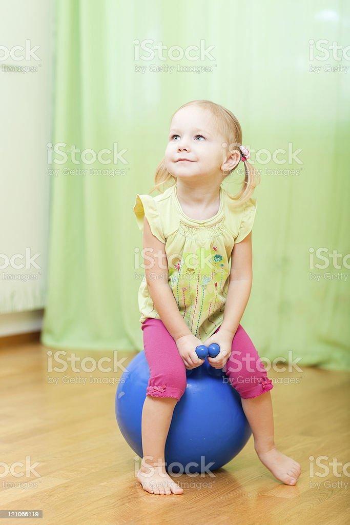 Toddler girl jumping on ball stock photo