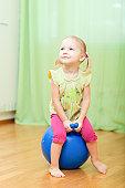 Toddler girl jumping on ball