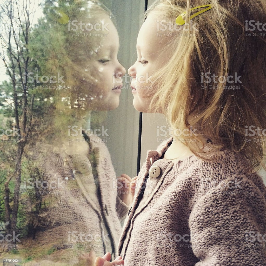 Toddler girl looking at her own reflection stock photo