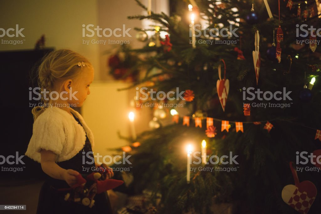 Toddler girl looking at the christmas tree stock photo